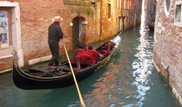 Gondolier along a canal through the houses of Venice - Italy